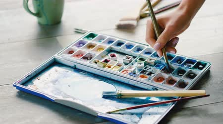 dips : Watercolor painting. Hand dipping brush in palette. Creative process Stock Footage