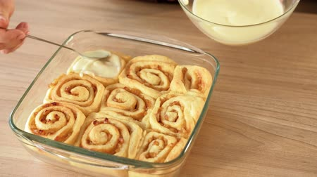 šlehačka : Bun rolls cooking recipe. Female chef adding icing to baked pastry Dostupné videozáznamy