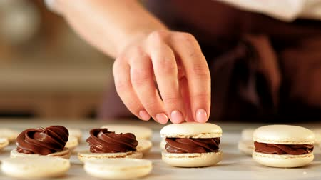macarons : Pastry cooking. Sweet dessert. Vanilla macarons with chocolate filling assembling