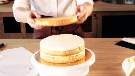 decorating : Cake shop business. Pastry chef assembling sponge cake and adding creamy filling
