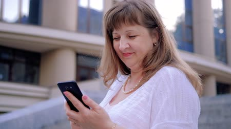 avançar : Modern technology. Easy online communication. Cheerful mature woman texting on smartphone.