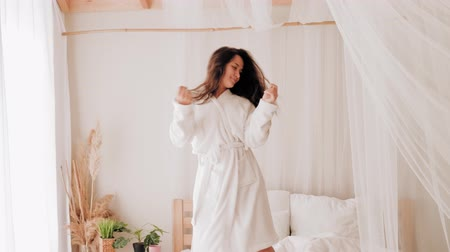 energický : Teenage home leisure. Fun entertainment joy. Energetic girl in bathrobe dancing on bed.