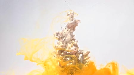 fuvalom : Ink drop in water. Molten lead. Glossy gray yellow paint mix motion on white background for intro. Stock mozgókép