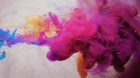 yellow ink : Ink blend in water. Floating vapor. Orange magenta pink haze motion on white background for intro.