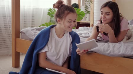 bestie : True friendship. Cooperation support care. Teen girl studying on tablet offering tea to bestie.
