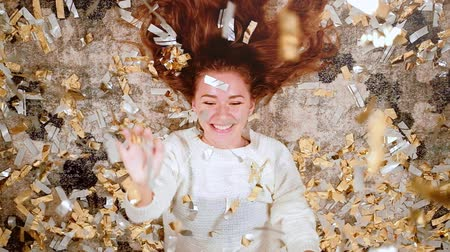 повод : Fancy party. Entertainment joy. Amused teen girl lying down on floor having fun in confetti rain.