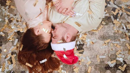 newyear : Romantic Christmas. Love affection. Happy couple lying down on floor in confetti rain smiling. Stock Footage