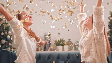 newyear : Fancy Christmas party. Holiday joy. Happy teen girls having fun throwing up shiny confetti. Stock Footage