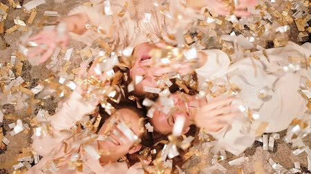 ralentir : Girls party. Fancy celebration. Joyful friends lying down in circle on floor in confetti rain. Vidéos Libres De Droits