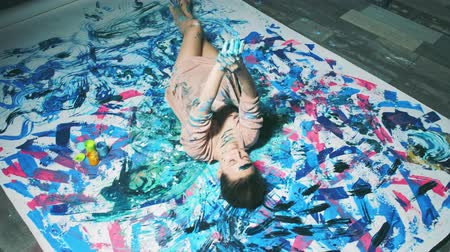 obsession : Art therapy. Mind healing. Relaxed woman in paint enjoying hand dance lying down on floor. Stock Footage
