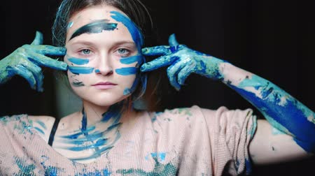 madness : Art power. Stress relief. Confident woman making lines on face with blue paint.