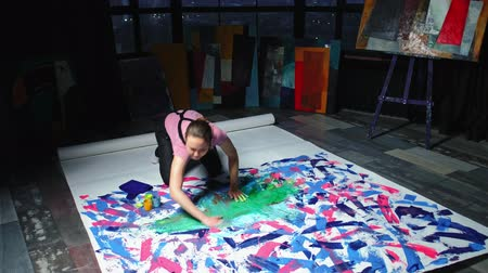 bluestone : Hand painting. Art art therapy. Enthusiastic woman creating abstract picture on floor in loft studio.