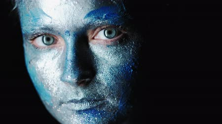 fotoshoot : Fashion glitter makeup. Dramatic beauty. Woman with face in blue shiny paint posing on dark background.