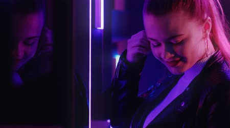 punker : Neon light portrait. Music party. Happy girl dancing looking at reflection in mirror purple glow. Stockvideo