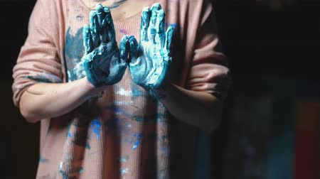 bluestone : Creative meditation. Spiritual power of art. Woman showing palms of hands dirty with blue paint.