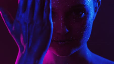 hidden face : Lights portrait. Right to privacy. Woman hiding half of glitter face with hand in pink blue glow.