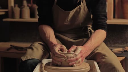 potter wheel : Ceramic art. Creative craft. Man hands shaping clay on potter wheel at workshop. Stock Footage