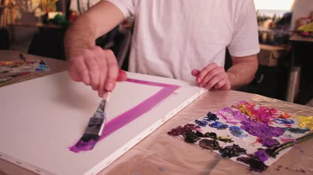 obra prima : Painting hobby. Craft activity. Male artist making purple lines with brush on canvas in studio.
