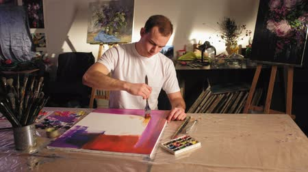 шедевр : Contemporary art. Inspiration imagination. Talented man painting colorful abstract picture in studio.