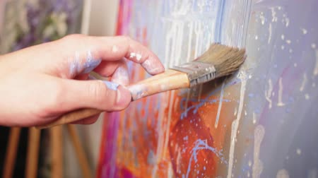 успокаивающий : Relaxing art. Soothing movement. Male hand smearing paint on colorful abstract picture with brush.