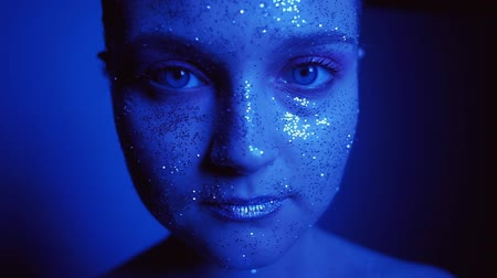 装飾品 : Neon light portrait. Skincare beauty. Woman with glitter face opening eyes slowly in blue glow. 動画素材