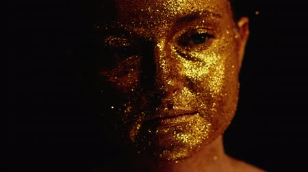 装飾品 : Creative glitter portrait. Skin procedure. Woman with golden sparkling face over black background. 動画素材
