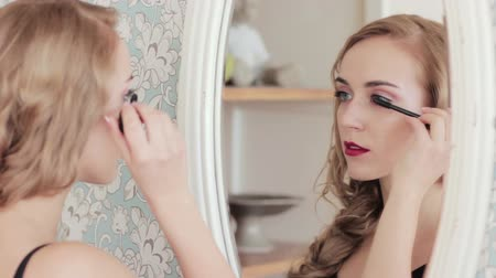 Makeup art. Decorative cosmetics. Beautiful woman applying mascara in mirror reflection. Stock Footage
