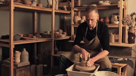 Ceramic art. Creative hobby. Skilled man molding clay on potter wheel at workshop.