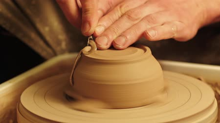 moldagem : Ceramics art. Creative hobby. Man hands carving clay pot bottom with cutter on wheel.