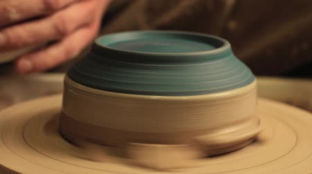 glinka : Pottery art. Creative hobby. Man hand using brush to apply clay over bowl spinning on wheel.