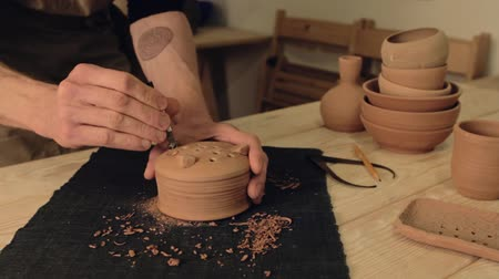 terrakotta : Ceramics art. Handmade manufacturing. Man hands drilling out holes in clay pot bottom. Stock mozgókép