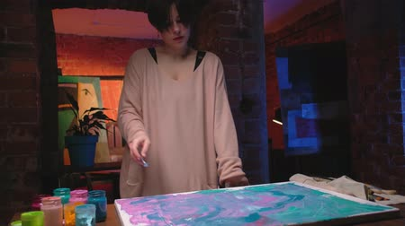 Painting hobby. Relaxing activity. Inspired woman creating abstract artwork in loft studio. Stock Footage