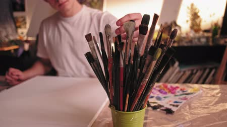 home studio : Art hobby. Creative leisure. Man choosing brush for painting new picture in studio.