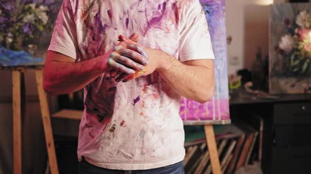 Art addiction. Inspiration creativity. Man rubbing hands with wet acrylic paint in studio.