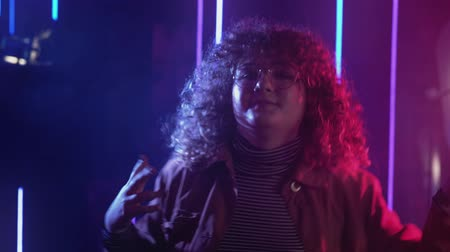 80s style girl. Disco party. Happy woman with curly hair enjoying dancing in blue pink neon lights.