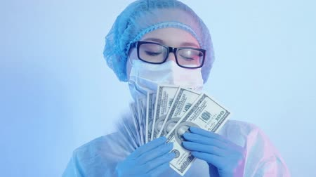 醫療保健 : Illegal medicine practice. Healthcare crime. Female doctor holding 100 US dollar cash fan.