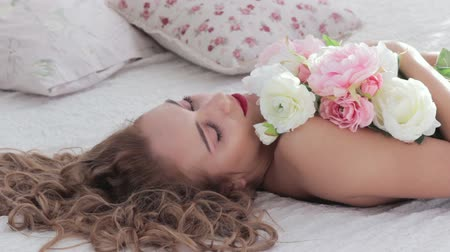 Feminine beauty. Body care wellness. Tender woman with peony flowers lying down on bed.