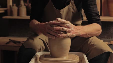 Pottery class. Art education. Male hands molding vase on wheel at workshop.