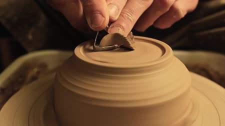 Ceramic art. Creative hobby. Male hands carving clay bowl bottom on spinning wheel.