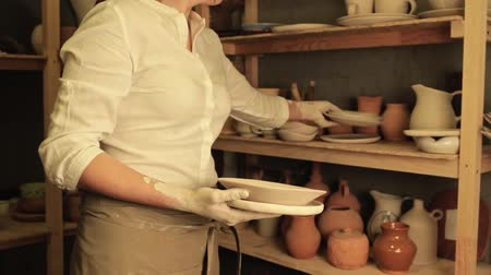 Pottery shop. Art business. Female artist collecting handmade clay plates from stack with ceramics.