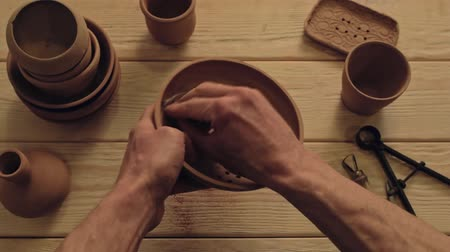 Pottery art. Handmade ceramics. Man hands polishing clay bowl at studio workplace. Stock Footage