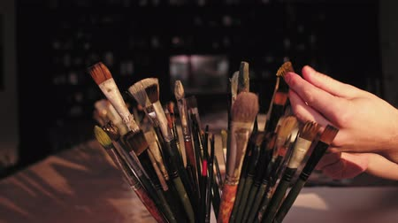 Painting supplies. Professional artist tools. Male hand picking up brush. Stock Footage