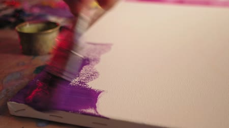 obra prima : Art therapy. Relaxation session. Male hand creating picture with brush purple paint on white canvas.