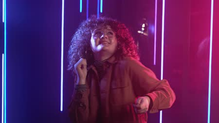 Neon girl. Night party. Smiling woman with curly hair enjoying dancing in blue pink illumination. Stock Footage