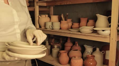 terrakotta : Pottery artist lifestyle. Handmade ceramics. Woman arranging clay plates on stack with jars.