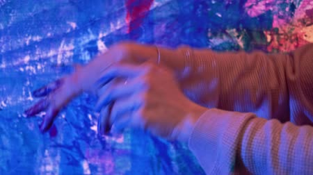 ziel : Hand dance. Stress relief. Female fingers in paint hypnotizing movements over blue abstract artwork. Stockvideo