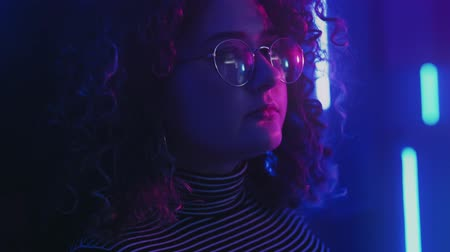 kıvırcık saçlar : Color light portrait. Nostalgia flashback. Pensive girl in eyeglasses in blue purple neon glow.