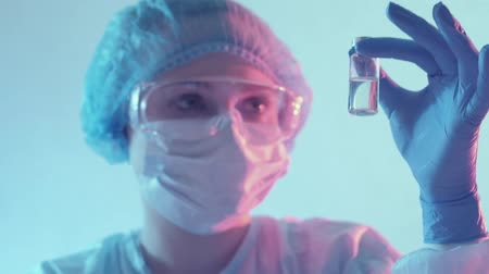анти : Clinical research. Innovative pharmaceuticals. Female technician in PPE testing drugs in vial.