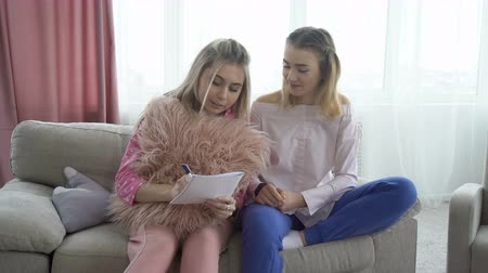 friendship bff. leisure pastime. friends communication writing in notebook. young teenage mates at home studying the fun way