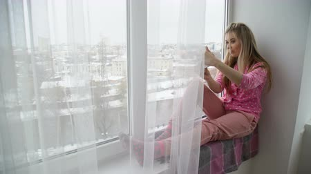 selfie modern youth lifestyle. online posting social network concept. young girl sitting on a windowsill taking photo Stock Footage